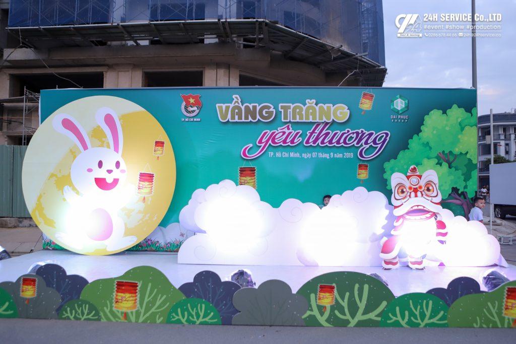Photobooth rực rỡ đặt bên cạnh cổng chào với hình ảnh con lân, thỏ ngọc, vầng trăng.