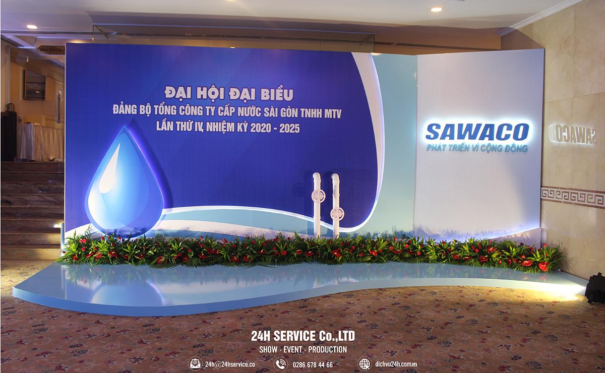 Booth chụp ảnh với điểm nhấn là logo SAWACO được tạo khối, viền led sáng cùng mô hình giọt nước và hệ thống cấp nước.